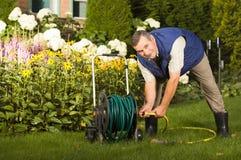 Quetschverbindenschlauch des älteren Mannes im Garten Lizenzfreie Stockbilder