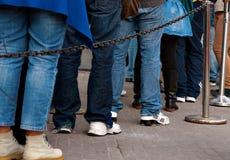 Queue. Legs of persons in casual dresses in queue Stock Image