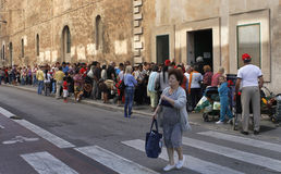 Queue at basic food distribution point. Needed. homeless or low rent people wait in a queue outside a church that distributes food in the spanish island of Stock Photography