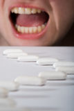 Queue of chewing gums heading to open mouth. Long queue of chewing gums heading to widely open mouth with teeth and tongue. Mouth are screaming or maybe smiling Royalty Free Stock Photo