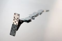 A queue of falling dominoes Stock Photo
