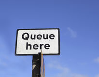 Queue here. Sign with text queue here in Great Brittain Stock Images