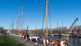 A queue of moored sailing ships in the port of Enkhuizen. In the wintertime those commercial sailing vessels overwinter is this hospitable harbour. Most of stock image