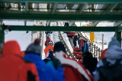 Queue of people on lift. Back view of people with snow tubes in queue on lift royalty free stock images