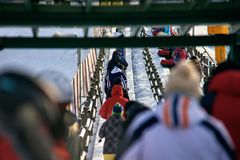 Queue of people on lift. Back view of people with snow tubes in queue on lift royalty free stock photo