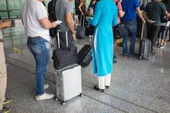 Queue of people in Noi Bai airport, Vietnam. Focus on female staff wearing Vietnamese long dress Ao Dai.  royalty free stock photos