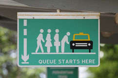 Queue sign. A 'Queue Starts Here' sign at a bus stop Royalty Free Stock Photos