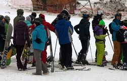 Queue of skiers on ski lift at ski resort. Skiing, slalom as russian youth craze. Russia, Perm - January 3, 2017: Queue of skiers on ski lift at ski resort royalty free stock photo