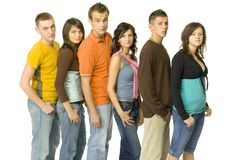 Queue of teenagers. Queue of waiting teenagers. Side view. They're looking at camera. White background royalty free stock photos