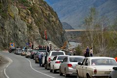 The queue of tourists on cars is waiting for the removal of heavy road equipment of stone rubble on the Chui tract in one of the m stock photo