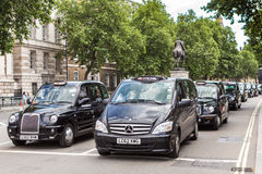 A queue of traditional British taxis. LONDON, UK - JUNE 11, 2014: A queue of traditional British taxis during a taxi drivers protest against Uber cabs Royalty Free Stock Images
