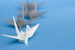 Queuing. A group of white and grey origami birds forming a queue stock photography