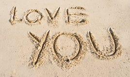 ?Quiérale? mensaje en la arena. foto de archivo