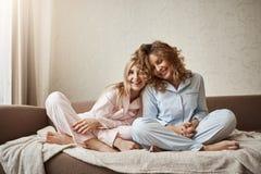 Qui peut comprendre mieux que la mère Deux belles filles s'asseyant sur le sofa dans les chemises de nuit, caresse, exprimant l'o Image libre de droits