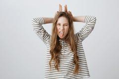 Qui s'inquiète, soit vous-même Portrait de la jeune femme sûre gaie montrant la langue, faisant des visages et tenant des mains d Photos stock