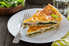 Quiche with arugula and bacon. Quiche with cheese, arugula and bacon on a table Stock Image