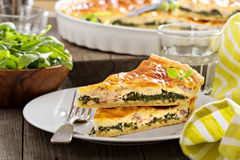Quiche with arugula and bacon. Quiche with cheese, arugula and bacon on a table Stock Images