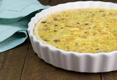 Quiche with cheese, bacon and mushroom on rustic wooden table - royalty free stock photo