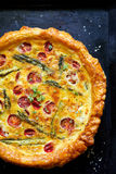 Quiche with cherry tomatoes and green asparagus on black background Stock Photos