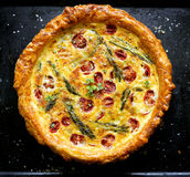Quiche with cherry tomatoes and green asparagus on black background Royalty Free Stock Photography