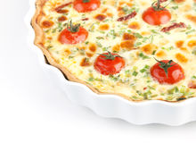 Quiche with cherry tomatoes and herbs on a white plate Stock Image