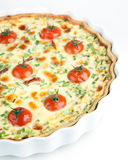 Quiche with cherry tomatoes and herbs on a white plate Stock Images