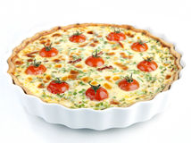 Quiche with cherry tomatoes and herbs on a white plate Royalty Free Stock Image