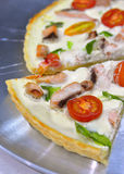 Quiche. Delicious variation for quiche pie and pizza - pie with thickened cream and cottage cheese, salmon, green capsicum and cherry tomatoes cut in halves Royalty Free Stock Photography