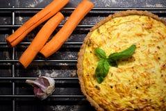 Quiche entera hecha en casa de la zanahoria del grano con el queso cremoso, la crema agria y el tocino adornados por la hoja de l Imagenes de archivo