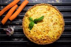 Quiche entera hecha en casa de la zanahoria del grano con el queso cremoso, la crema agria y el tocino adornados por la hoja de l Imagen de archivo