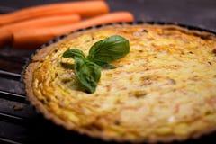 Quiche entera hecha en casa de la zanahoria del grano con el queso cremoso, la crema agria y el tocino adornados por la hoja de l Foto de archivo