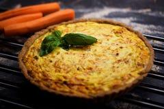 Quiche entera hecha en casa de la zanahoria del grano con el queso cremoso, la crema agria y el tocino adornados por la hoja de l Imagen de archivo libre de regalías
