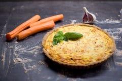 Quiche entière faite maison de carotte de grain avec le fromage fondu, la crème sure et le lard décorés par la feuille du basilic Image libre de droits