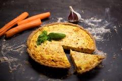 Quiche entière faite maison de carotte de grain avec le fromage fondu, la crème sure et le lard décorés par la feuille du basilic Photo libre de droits