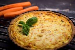 Quiche entière faite maison de carotte de grain avec le fromage fondu, la crème sure et le lard décorés par la feuille du basilic Images libres de droits