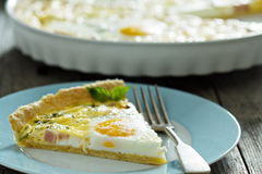 Quiche with ham and eggs. Quiche with ham, green onion and whole eggs Stock Photography
