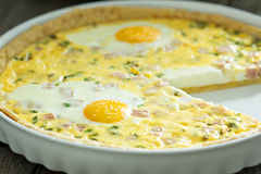 Quiche with ham and eggs. Quiche with ham, green onion and whole eggs Stock Images