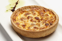 Quiche Lorraine. (with bacon and eggs) on a white plate Royalty Free Stock Photos