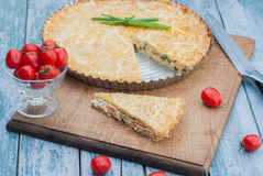Quiche Lorraine. Appetizing pie quiche Lorraine with cherry tomatoes in a small bowl. Fresh organic cherry tomatoes. Blue background, which is stylized as the Royalty Free Stock Photography