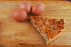 Quiche lorraine with eggs on wooden board. Quiche lorraine with eggs on chopping board Royalty Free Stock Photography