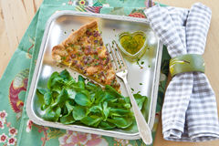 Quiche Lorraine and lamb's lettuce. Piece of quiche lorraine and fresh lamb's lettuce Royalty Free Stock Photos