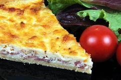 Quiche Lorraine. Quiche Lorraine with lettuce and cherry tomatoes on a black plate Stock Photo