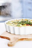 Quiche lorraine. A picture of a freshly baked quiche served on a wooden chopping board Royalty Free Stock Image