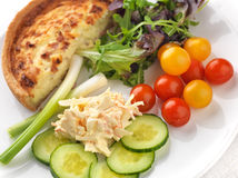 Quiche Lorraine and salad. Including ripe cherry tomatoes, cucumber, spring onions, coleslaw and salad leaves Stock Photography