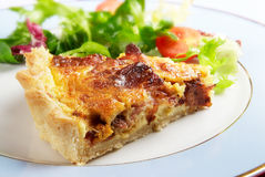Quiche lorraine slice. A slice of bacon and cheese quiche lorraine on a blue plate with crisp leafy salad dressing Stock Image