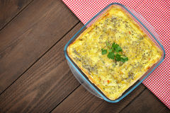 Quiche lorraine. In square baking form on wooden background, top view Stock Image
