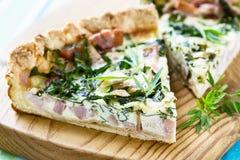 Quiche lorraine, Torte mit einem geräucherten Speck, Käse und Spinat Lizenzfreie Stockfotografie