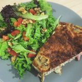 Quiche pastry with green salad on a plate on a Mediterranean diet food Royalty Free Stock Photos
