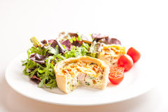 Quiche Plate Isolated. Small Quiche with ham, broccoli and leek on a plate with salad and tomatos showing whole plate isolated on white Stock Images