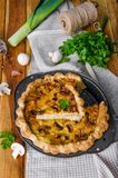 Quiche on puff pastry with leek, meat and mushrooms. Rustic style royalty free stock image